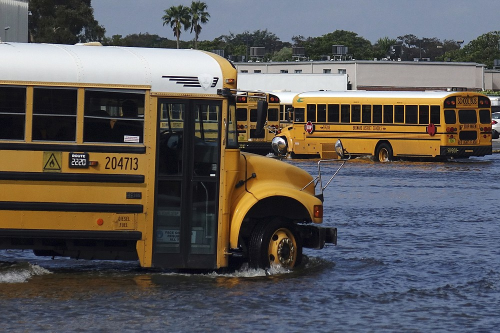 A school bus drives through the flooded parking lot of the Browad School District Central Depot in Oakland Park, Fla., Tuesday, Nov. 10, 2020. Tropical Storm Eta is squatting off western Cuba, and forecasters say it's unclear where it might strike land again. It dumped torrential rain on Cuba and South Florida, flooding entire neighborhoods. (Joe Cavaretta/South Florida Sun-Sentinel via AP)