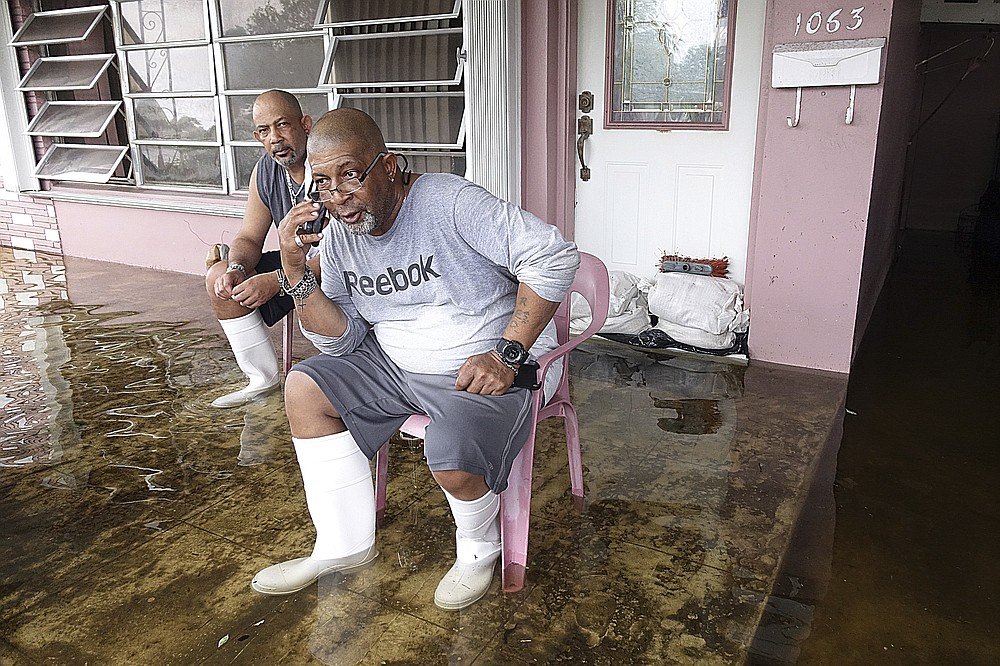 Dalvin, left, and his brother Eric Gaines sit on the porch of thier flooded home in Melrose Park in Fort Lauderdale, Fla., Tuesday, Nov. 10, 2020. Tropical Storm Eta is squatting off western Cuba, and forecasters say it's unclear where it might strike land again. It dumped torrential rain on Cuba and South Florida, flooding entire neighborhoods. (Joe Cavaretta/South Florida Sun-Sentinel via AP)
