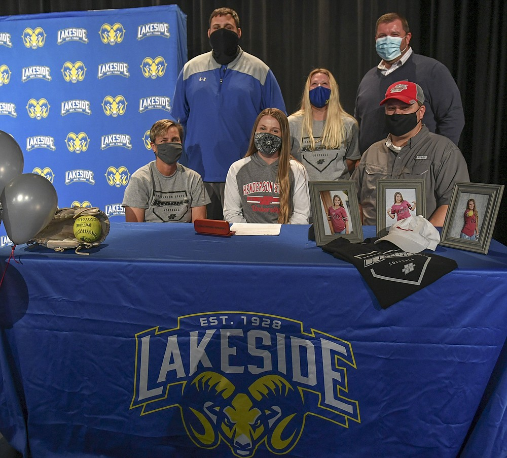 Lakeside senior Erika Bittinger, center, is joined by, from left, her mother Lanea, Lakeside head softball coach Josh Bradley, sister Emylee,  principal Darin Landry and father Bobby as she signs a letter of intent to play softball with Henderson State University Wednesday. - Photo by Grace Brown of The Sentinel-Record