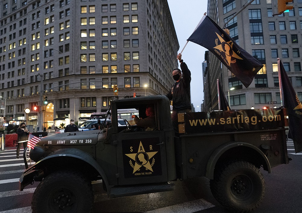 A man waves a flag as he stands in the back of a military vehicle during a Veterans Day parade, Wednesday, Nov. 11, 2020 in New York. The 100-vehicle parade, with no spectators, was held during the coronavirus pandemic to maintain the 101-year tradition of veterans marching on Fifth Avenue. The U.S. has recorded about 10.3 million confirmed infections, with new cases soaring to all-time highs of well over 120,000 per day over the past week. (AP Photo/Mark Lennihan)