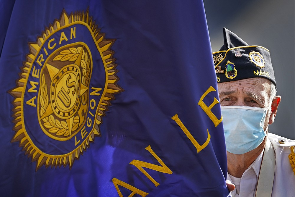 Dick Bell, the post adjutant of the American Legion Post 155, wears a face covering to help prevent the spread of the coronavirus while taking part in a Veterans Day ceremony, Wednesday, Nov. 11, 2020, in Naples, Maine. The U.S. has recorded about 10.3 million confirmed infections, with new cases soaring to all-time highs of well over 120,000 per day over the past week. (AP Photo/Robert F. Bukaty)
