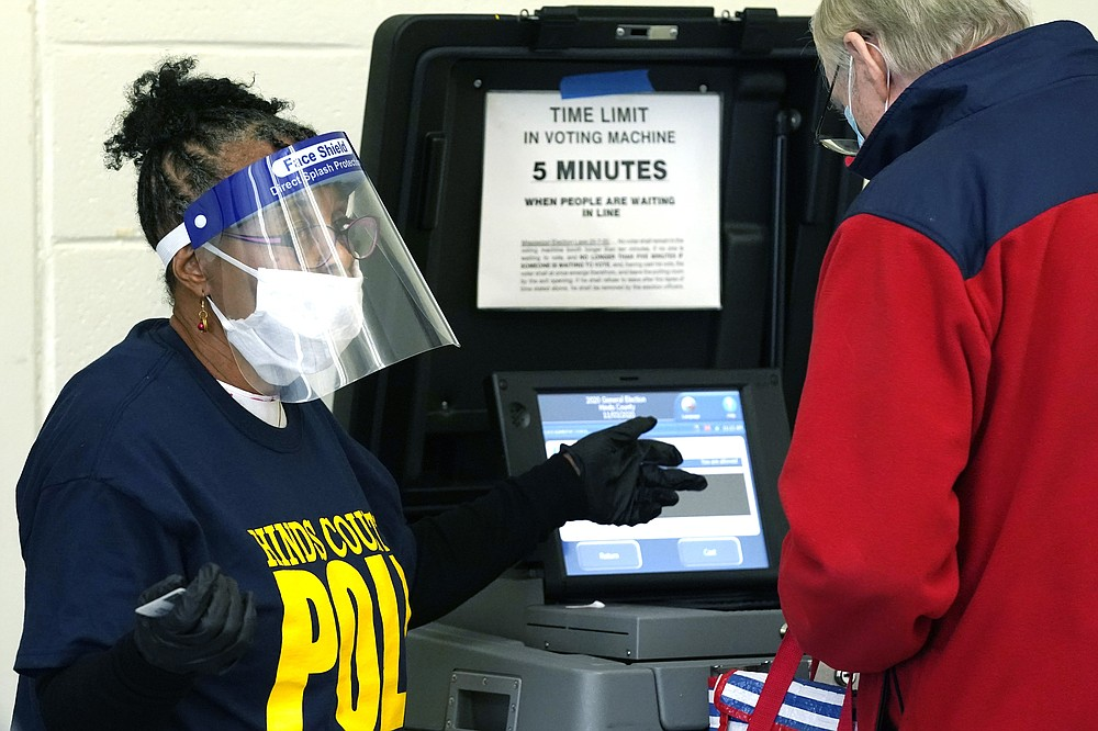 FILE - In this Nov. 3, 2020, file photo, Precinct 36 poll worker Vivian Bibens wears personal protective equipment as she explains the purpose of the ballot scanner to a voter on Election Day in Jackson, Miss. The 2020 presidential election had all the makings of a looming disaster: fears of Russian meddling, violence at the polls, voter intimidation and poll workers fleeing their posts over the coronavirus. But the election was largely smooth, in large part because 107 million voters that cast their ballots early and took the pressure off Election Day operations. (AP Photo/Rogelio V. Solis, File)