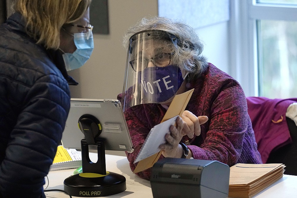 FILE - In this Oct. 28, 2020, file photo, poll worker Alice Machinist, of Newton, Mass., right, wears a mask and shield out of concern for the coronavirus while assisting a voter, left, with a ballot during early in-person general election voting at the Newton Free Library, in Newton, Mass. The 2020 presidential election had all the makings of a looming disaster: fears of Russian meddling, violence at the polls, voter intimidation and poll workers fleeing their posts over the coronavirus. But the election was largely smooth, in large part because 107 million voters that cast their ballots early and took the pressure off Election Day operations. (AP Photo/Steven Senne, File)