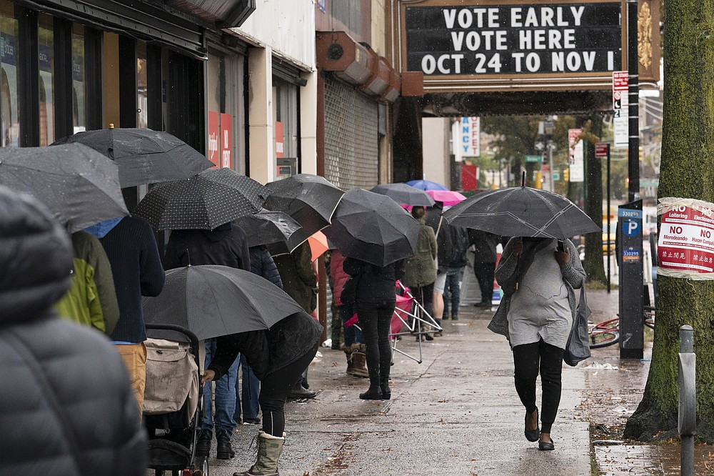 FILE - In this Oct. 30, 2020, file photo, people under umbrellas line up for early voting in the Brooklyn borough of New York. The 2020 presidential election had all the makings of a looming disaster: fears of Russian meddling, violence at the polls, voter intimidation and poll workers fleeing their posts over the coronavirus. But the election was largely smooth, in large part because 107 million voters that cast their ballots early and took the pressure off Election Day operations. (AP Photo/Mark Lennihan, File)