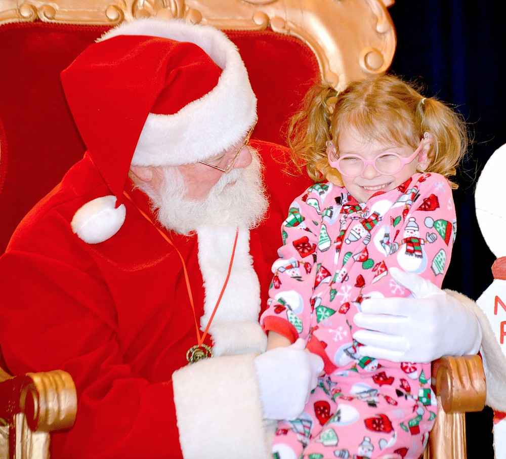 File photo Catherine Graves, 5, of Siloam Springs, was all giggles as she sat on Santa's lap during the Heritage League Breakfast with Santa event on Saturday morning.