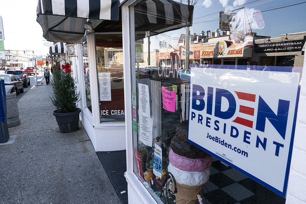 """A sign for President-elect Joe Biden is displayed in a shop window, Friday, Nov. 13, 2020, in Rehoboth Beach, Del. This resort town known for Atlantic waves that are sometimes surfable, fresh-cut French fries and a 1-mile wooden boardwalk that dates back to the 1870s has long prided itself on being the """"Nation's Summer Capital."""" It may soon sport a beach White House. (AP Photo/Alex Brandon)"""