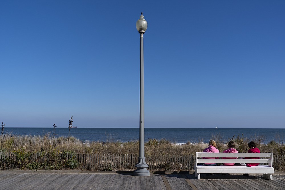 """People enjoy a view of the beach, Friday, Nov. 13, 2020, in Rehoboth Beach, Del. This resort town known for Atlantic waves that are sometimes surfable, fresh-cut French fries and a 1-mile wooden boardwalk that dates back to the 1870s has long prided itself on being the """"Nation's Summer Capital."""" It may soon sport a beach White House. (AP Photo/Alex Brandon)"""