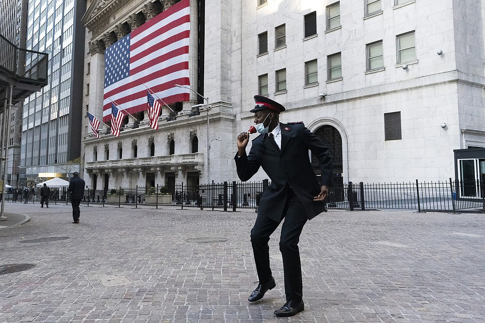 Captain Chaka Watch with the Salvation Army plays lip syncs in front of the New York Stock Exchange, Monday, Nov. 16, 2020, in New York. Stock markets are rallying on news that a second coronavirus vaccine shows promise. (AP Photo/Mark Lennihan)
