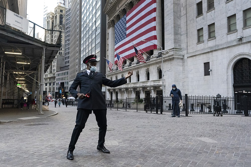 Captain Chaka Watch with the Salvation Army plays air guitar in front of the New York Stock Exchange, Monday, Nov. 16, 2020, in New York. Stock markets are rallying on news that a second coronavirus vaccine shows promise. (AP Photo/Mark Lennihan)