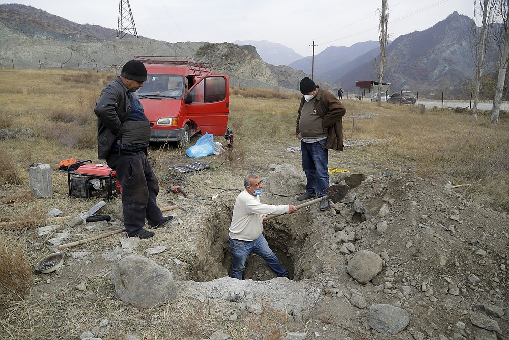 Ethnic Armenians dig up the grave to pull out a coffin with the body of their relative Sergei Gabrilyan, to repatriate his remains to Armenia, in Kalbajar in separatist region of Nagorno-Karabakh, Monday, Nov. 16, 2020. It is unclear when any civilians might try to settle in Karvachar, which will now be known by its Azeri name Kalbajar, or elsewhere. Armenians who are going to leave separatist region of Nagorno-Karabakh dig up the remains of their ancestors to bring them from the territory, which is to be handed over to Azerbaijanis. (AP Photo/Sergei Grits)