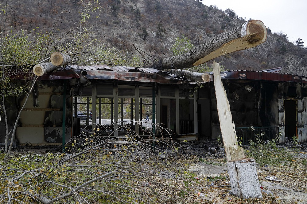 "A man walks past a damaged gasoline station in Kalbajar in separatist region of Nagorno-Karabakh, Monday, Nov. 16, 2020. It is unclear when any civilians might try to settle in Karvachar, which will now be known by its Azeri name Kalbajar, or elsewhere. Azerbaijan on Sunday postponed taking control of a territory ceded by Armenian forces in a cease-fire agreement, but denounced civilians leaving the area for burning houses and committing what it called ""ecological terror."" (AP Photo/Sergei Grits)"