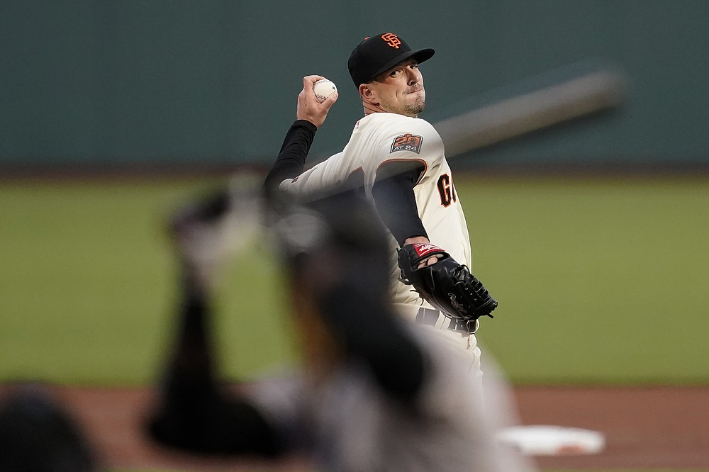 San Francisco Giants' Drew Smyly, rear, pitches against Colorado Rockies' Raimel Tapia during the first inning of a baseball game in San Francisco, Tuesday, Sept. 22, 2020. (AP Photo/Jeff Chiu)