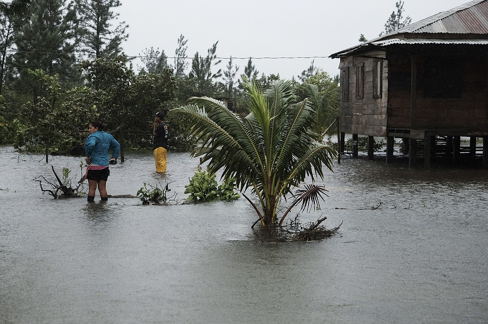 Residents stand outside a home surrounded by floodwaters brought on by Hurricane Eta in Wawa, Nicaragua, Tuesday, Nov. 3, 2020. Eta slammed into Nicaragua's Caribbean coast with potentially devastating winds Tuesday, while heavy rains thrown off by the Category 4 storm already were causing rivers to overflow across Central America. (AP Photo/Carlos Herrera)