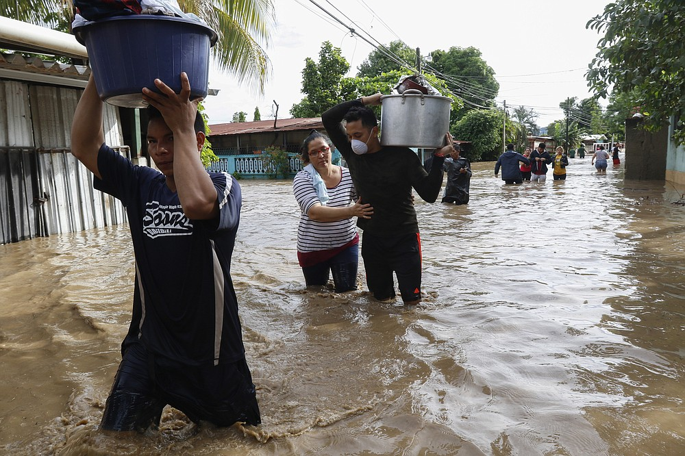 Residents wade through floodwaters carrying their belongings in the neighborhood of Suyapa, Honduras, Thursday, Nov. 5, 2020. The storm that hit Nicaragua as a Category 4 hurricane on Tuesday had become more of a vast tropical rainstorm, but it was advancing so slowly and dumping so much rain that much of Central America remained on high alert. (AP Photo/Delmer Martinez)