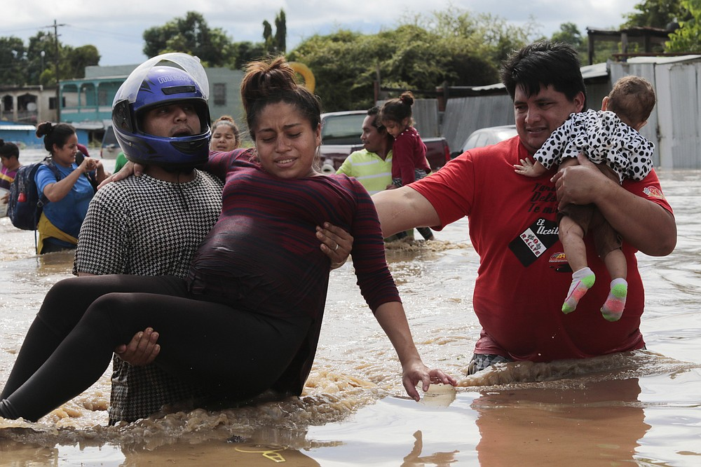 A pregnant woman is carried out of an area flooded by water brought by Hurricane Eta in Planeta, Honduras, Thursday, Nov. 5, 2020. The storm that hit Nicaragua as a Category 4 hurricane on Tuesday had become more of a vast tropical rainstorm, but it was advancing so slowly and dumping so much rain that much of Central America remained on high alert. (AP Photo/Delmer Martinez)