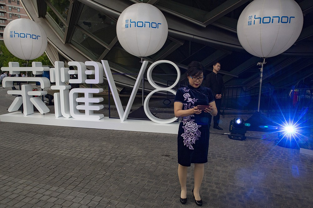 An attendee at a launch event for Huawei's Honor brand mobile phone stands near the brand logo in Beijing, China, Tuesday, May 10, 2016. In an announcement Tuesday, Nov. 17, 2020, Chinese tech giant Huawei says it is selling its budget-price Honor smartphone brand in an effort to rescue the struggling business from damaging U.S. sanctions imposed on its parent company. (AP Photo/Ng Han Guan)