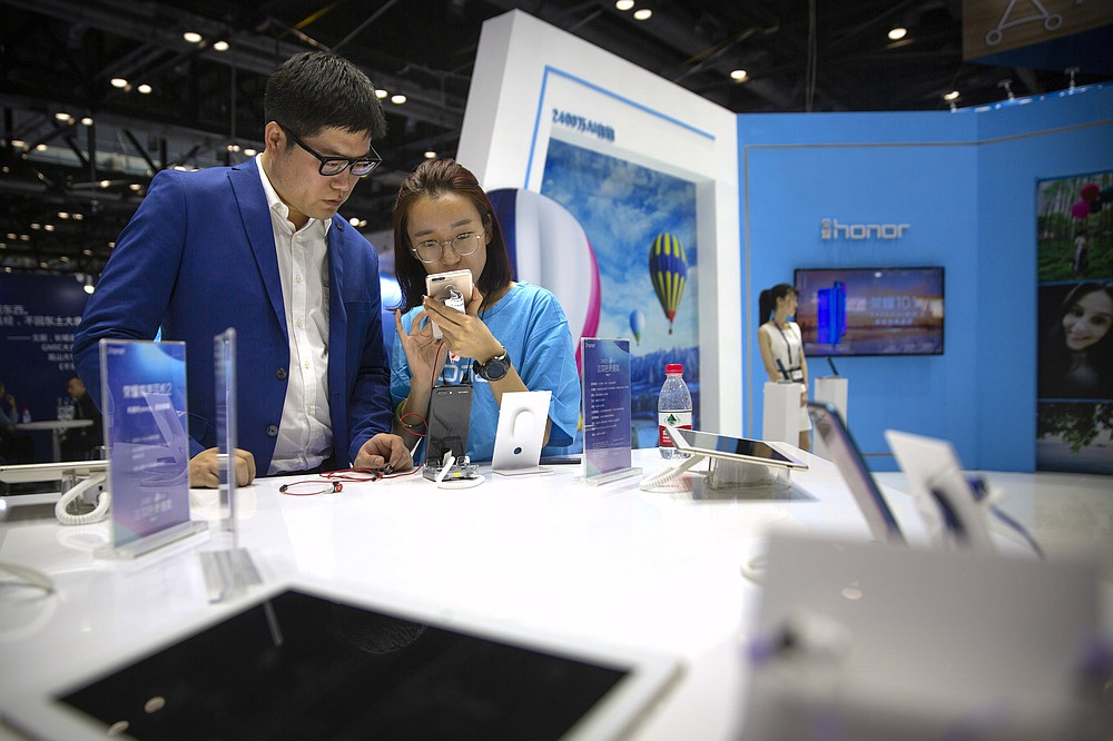 A staff member talks to a visitor at a booth for Chinese smartphone brand Honor at the Global Mobile Internet Conference in Beijing on April 26, 2018. In an announcement Tuesday, Nov. 17, 2020, Chinese tech giant Huawei says it is selling its budget-price Honor smartphone brand in an effort to rescue the struggling business from damaging U.S. sanctions imposed on its parent company. (AP Photo/Mark Schiefelbein)