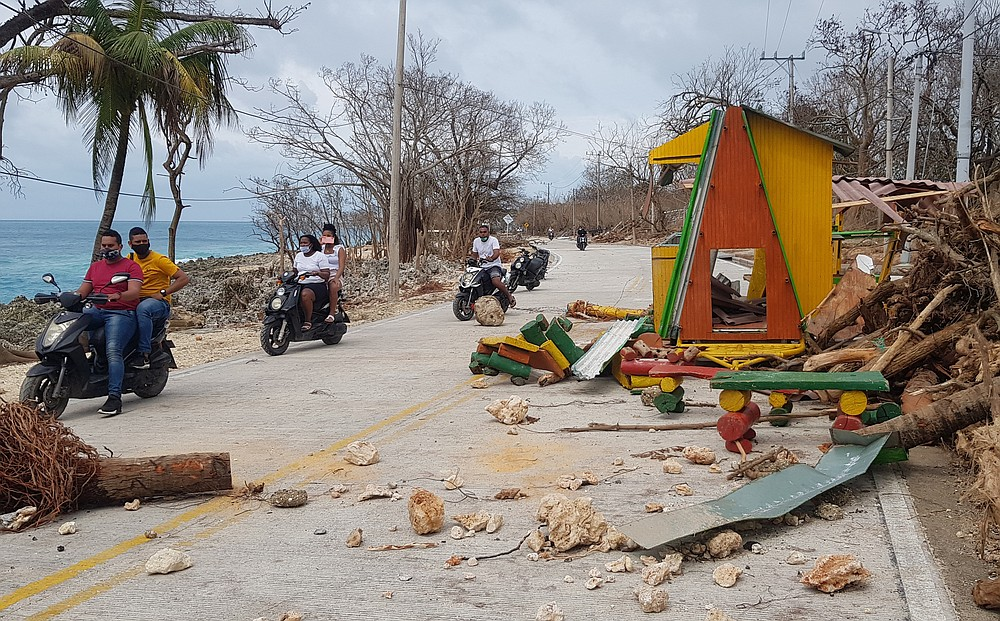 Motorcyclists pass debris on the road after the passing of Hurricane Iota on San Andres Island, Colombia, Tuesday, Nov. 17, 2020. Iota moved over the Colombian archipelago of San Andres, Providencia and Santa Catalina, off Nicaragua's coast, as a Category 5 hurricane. (AP Photo/Christian Quimbay)