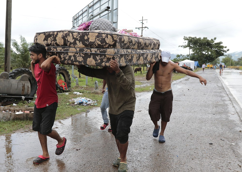 Neighbors help each other as they evacuate the area before Hurricane Iota makes landfall in San Manuel Cortes, Honduras, Monday, November 16, 2020. Hurricane Iota rapidly strengthened into a Category 5 storm that is likely to bring catastrophic damage to the same part of Central America already battered by a powerful Hurricane Eta less than two weeks ago. (AP Photo/Delmer Martinez)