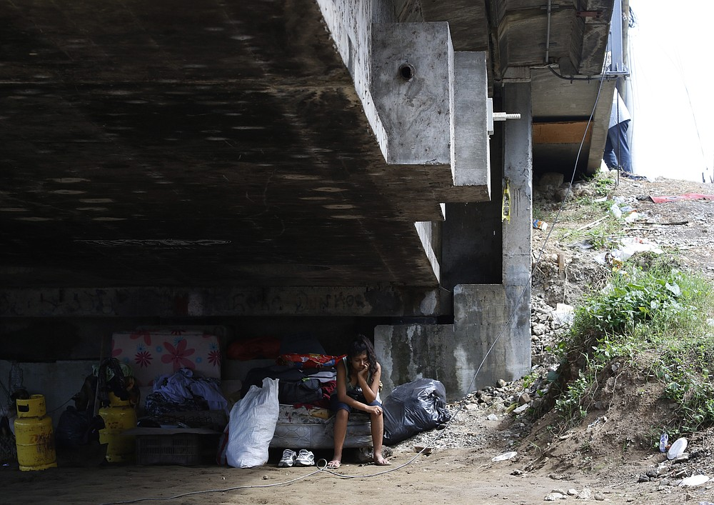 Mileydi Duarte, who was evacuated today by her family, rests under a highway bridge as she waits for space at a shelter before Hurricane Iota makes landfall in El Progreso Yoro, Honduras, Monday, November 16, 2020. Hurricane Iota rapidly strengthened into a Category 5 storm that is likely to bring catastrophic damage to the same part of Central America already battered by a powerful Hurricane Eta less than two weeks ago. (AP Photo/Delmer Martinez)