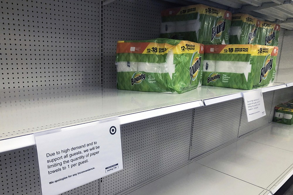 The quantity of paper towels customers can buy is listed at a Target Store, Tuesday, Nov. 17, 2020, in Bloomington, Minn. A surge of new coronavirus cases in the U.S. is sending people back to stores to stockpile again, leaving shelves bare and forcing retailers to put limits on purchases. (AP Photo/Jim Mone)