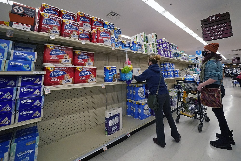 A woman buys toilet paper at a market in Mount Lebanon, Pa, on Tuesday, Nov. 17, 2020. A surge of new coronavirus cases in the U.S. is sending people back to stores to stockpile again, leaving shelves bare and forcing retailers to put limits on purchases. (AP Photo/Gene J. Puskar)