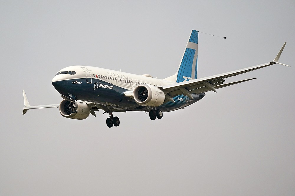 FILE - In this Wednesday, Sept. 30, 2020, file photo, a Boeing 737 Max jet, piloted by Federal Aviation Administration Chief Steve Dickson, prepares to land at Boeing Field following a test flight in Seattle. The FAA is poised to clear the Boeing 737 Max to fly again after grounding the jets for nearly two years due to a pair of disastrous crashes that killed 346 people. (AP Photo/Elaine Thompson, File)