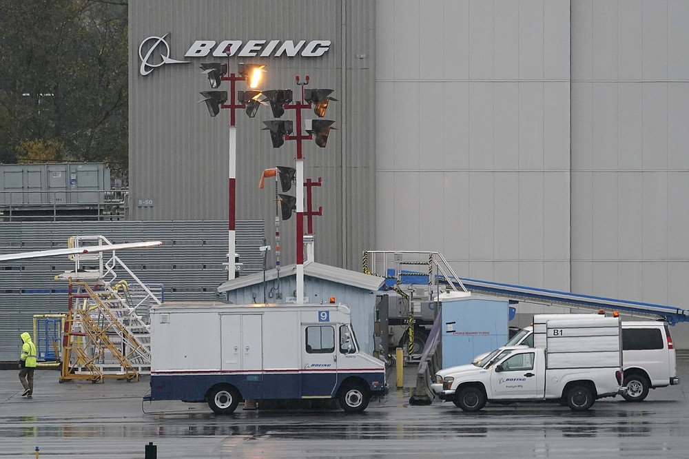 Boeing vehicles are parked near a worker at Renton Municipal Airport, Wednesday, Nov. 18, 2020, next to the Boeing assembly facility in Renton, Wash., where 737 Max airplanes are made. After nearly two years and a pair of deadly crashes, the U.S. Federal Aviation Administration announced Wednesday that the 737 Max has been cleared for flight after regulators around the world grounded the Max in March 2019, after the crash of an Ethiopian Airlines jet. (AP Photo/Ted S. Warren)