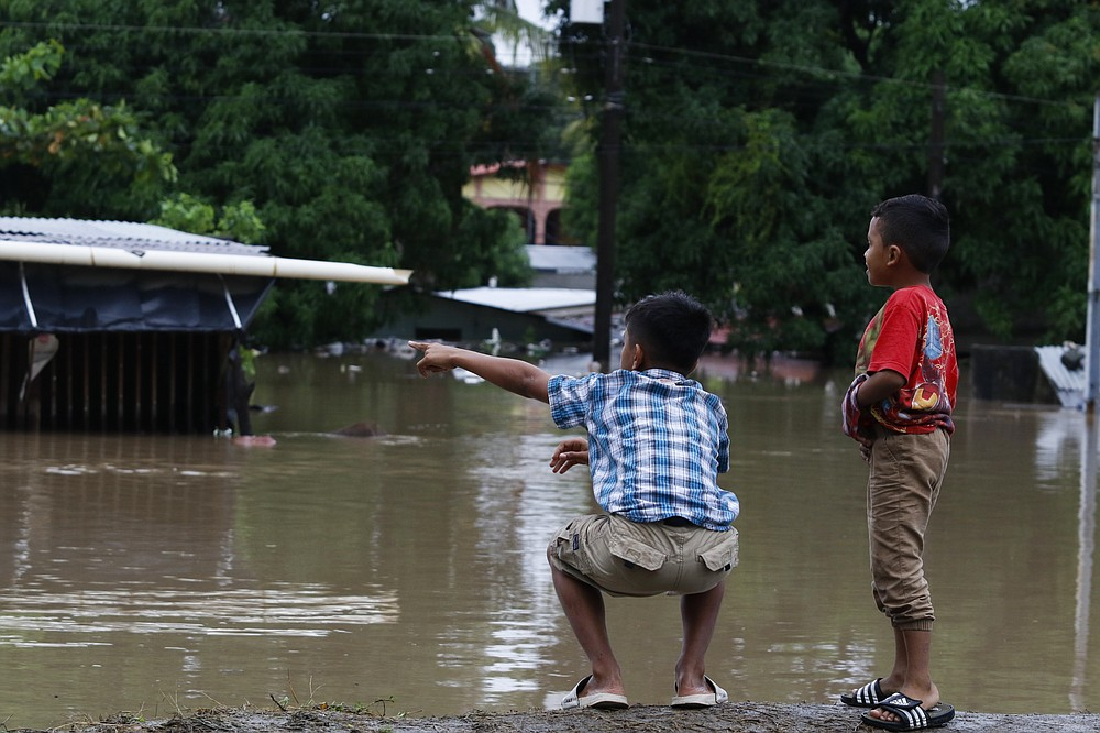 Children look at a flooded residential area near a river after the passing of Iota in La Lima, Honduras, Wednesday, Nov. 18, 2020. Iota flooded stretches of Honduras still underwater from Hurricane Eta, after it hit Nicaragua Monday evening as a Category 4 hurricane and weakened as it moved across Central America, dissipating over El Salvador early Wednesday. (AP Photo/Delmer Martinez)