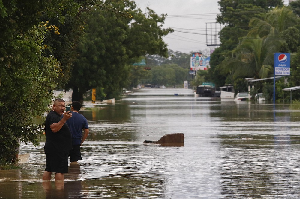 Men wade through a flooded street after the passing of Iota in La Lima, Honduras, Wednesday, Nov. 18, 2020. Iota flooded stretches of Honduras still underwater from Hurricane Eta, after it hit Nicaragua Monday evening as a Category 4 hurricane and weakened as it moved across Central America, dissipating over El Salvador early Wednesday. (AP Photo/Delmer Martinez)