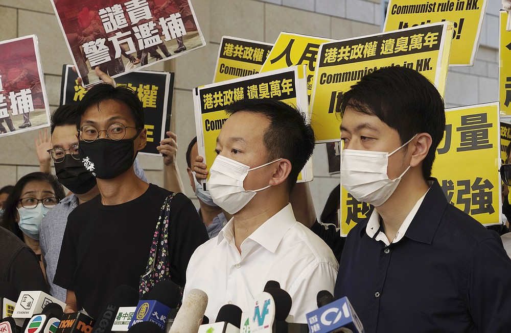 Pro-democracy lawmakers, from left, Eddie Chu, Raymond Chan and Ted Hui speak outside a local court in Hong Kong, Thursday, Nov. 19, 2020. Three former pro-democracy lawmakers appeared in court Thursday, one day after they were arrested for disrupting the legislature during debate on a national anthem bill earlier this year. (AP Photo/Vincent Yu)