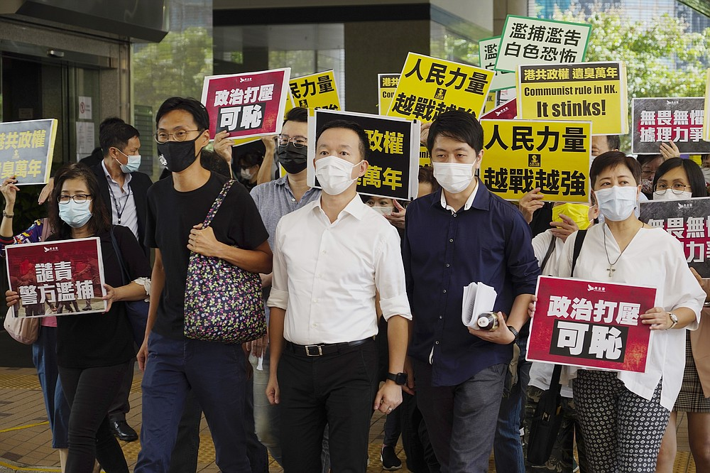 Pro-democracy lawmakers, from second left to right, Eddie Chu, Raymond Chan, and Ted Hui walk with supporters at a local court in Hong Kong, Thursday, Nov. 19, 2020. Three former pro-democracy lawmakers appeared in court Thursday, one day after they were arrested for disrupting the legislature during debate on a national anthem bill earlier this year. (AP Photo/Vincent Yu)
