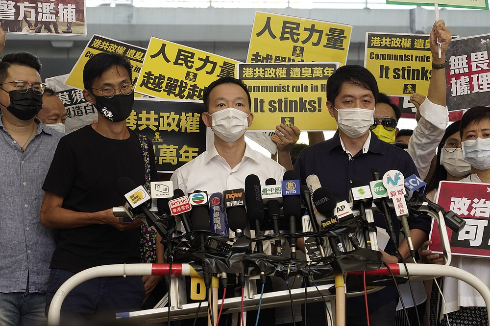 Pro-democracy lawmakers, from second left to right; Eddie Chu, Raymond Chan and Ted Hui speak outside a local court in Hong Kong Thursday, Nov. 19, 2020. Three former pro-democracy lawmakers appeared in court Thursday, one day after they were arrested for disrupting the legislature during debate on a national anthem bill earlier this year. (AP Photo/Vincent Yu)