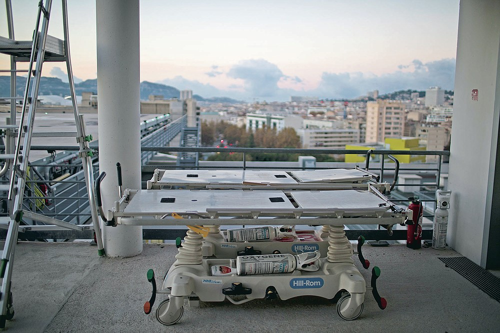 Portable intensive care beds with oxygen tanks are pictured on the rooftop of the La Timone hospital as the sun rises in Marseille, southern France, Friday, Nov. 13, 2020. France is more than two weeks into its second coronavirus lockdown, and intensive care wards have been over 95% capacity for more than 10 days now. Marseille has been submerged with coronavirus cases since September. (AP Photo/Daniel Cole)