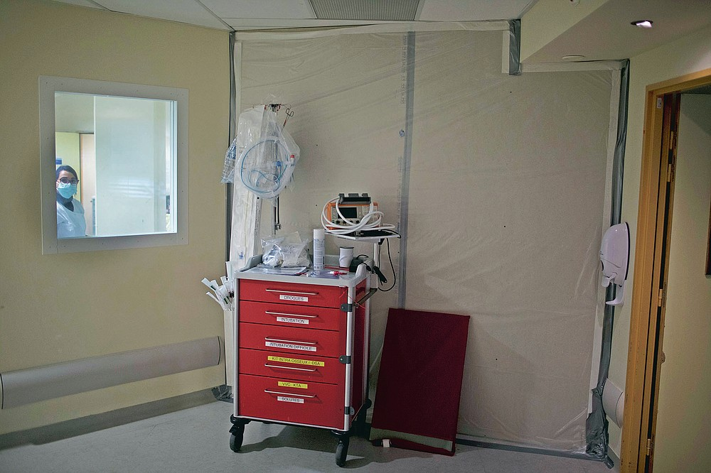 A fiberboard barricade fastened to a hospital corridor with duct tape seals off an acute care wing that was only recently refashioned into a makeshift COVID-19 ICU ward at the La Timone hospital in Marseille, southern France, Thursday, Nov. 12, 2020. (AP Photo/Daniel Cole)
