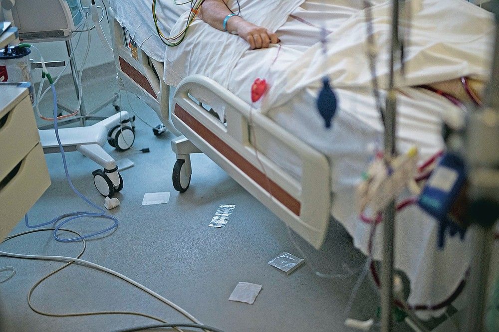Used surgical cloths and plastic wrappers lie beneath the bed of a 61-year old COVID-19 patient after medical staff provided care in the main ICU of the La Timone hospital in Marseille, southern France, Thursday, Nov. 12, 2020. (AP Photo/Daniel Cole)