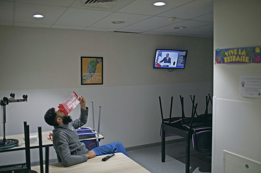 A nurse finishes a snack as a speech by French Prime Minister Jean Castex is played on the news in the ICU break room at the La Timone hospital in Marseille, southern France, Thursday, Nov. 12, 2020. Marseille has been submerged with coronavirus cases since September. The port city, on France's Mediterranean coast, was spared the worst of the virus last spring only to be hit with a vengeance as the summer vacation wound down. (AP Photo/Daniel Cole)