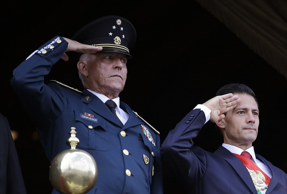 FILE - In this Sept. 16, 2016 file photo, Defense Secretary Gen. Salvador Cienfuegos, left, and Mexico's President Enrique Pena Nieto, salute during the annual Independence Day military parade in Mexico City's main square. U.S. prosecutors on Wednesday, Nov. 18, 2020, formally dropped a drug trafficking and money laundering case against Gen. Cienfuegos, a decision that came after Mexico threatened to cut off cooperation with U.S. authorities unless the general was sent home. (AP Photo/Rebecca Blackwell, File)