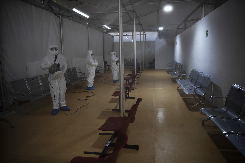 Sanitation technicians disinfect a tent used to test patients for COVID-19 at the Ajusco Medio General Hospital in Mexico City, Thursday, Nov. 19, 2020. (AP Photo/Marco Ugarte)