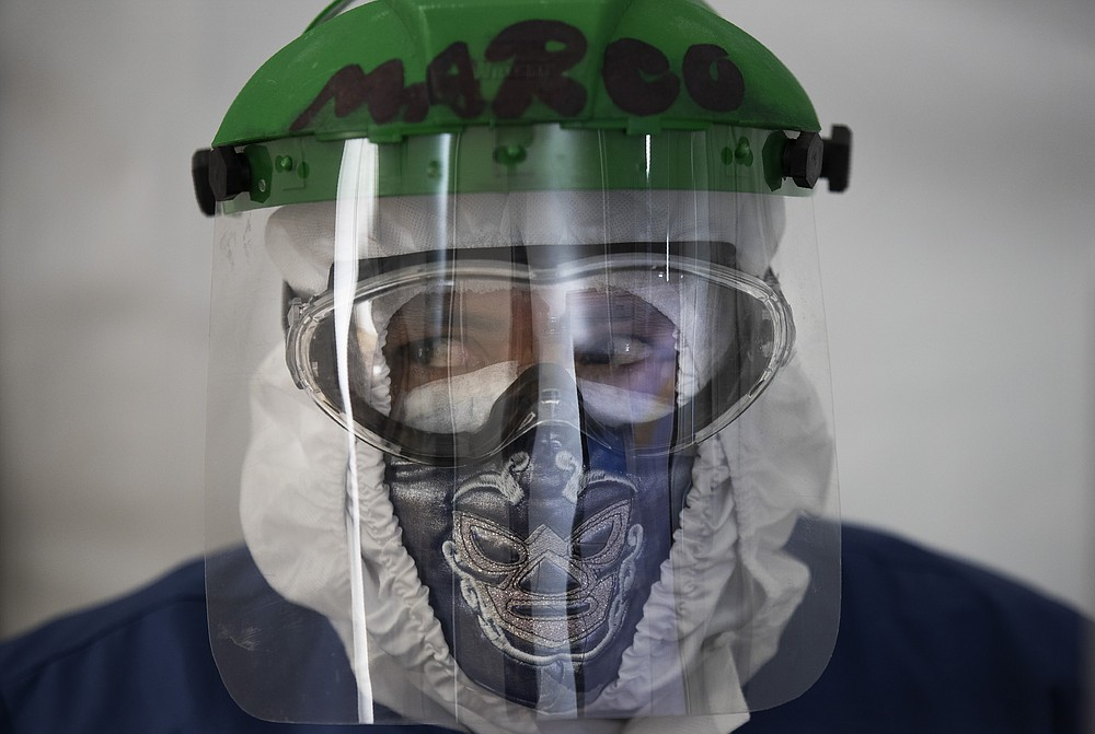 Healthcare worker Marco Antonio Galicia wears a protective face mask designed with a Mexican wrestler motif, in a ward designated for COVID-19 patients, at the Ajusco Medio General Hospital in Mexico City, Thursday, Nov. 19, 2020. (AP Photo/Marco Ugarte)