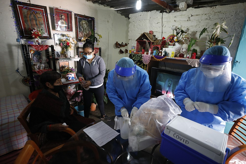 Doctors Delia Caudillo, center, and Monserrat Castaneda, prepare to conduct a COVID-19 test on 82-year-old Modesta Caballero Serrano, as her granddaughter gives her antibacterial gel, at her home in the Venustiano Carranza borough of Mexico City, Thursday, Nov. 19, 2020. (AP Photo/Rebecca Blackwell)