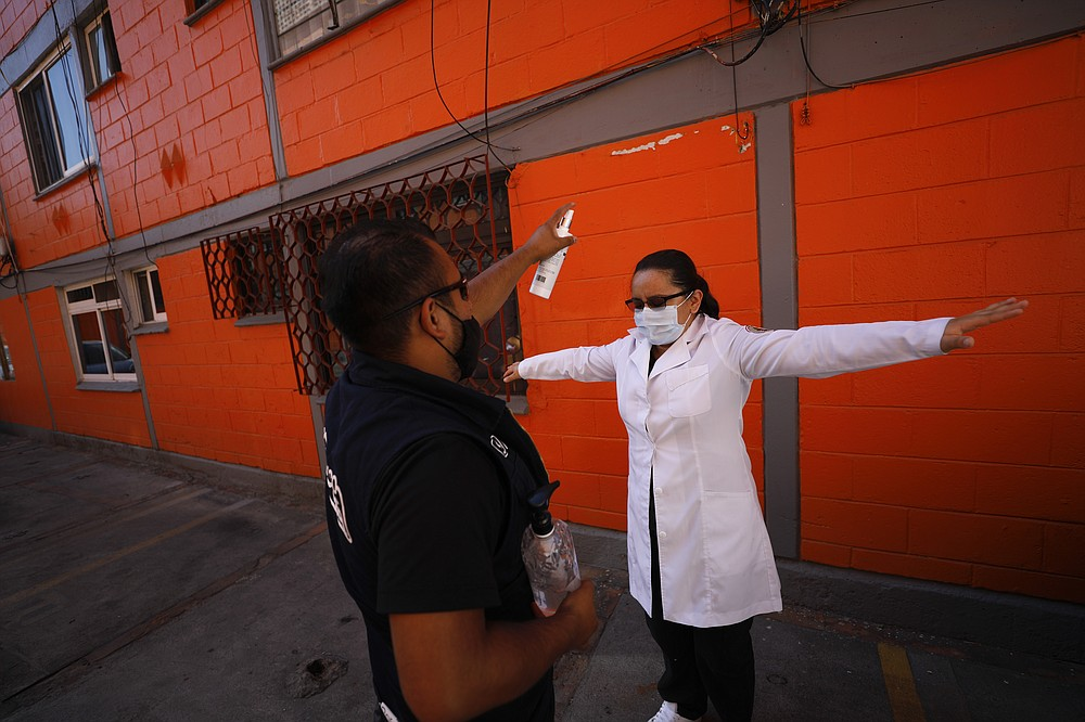 Dr. Monserrat Castaneda is sprayed with a disinfectant after conducting a COVID-19 test inside a home, in the Venustiano Carranza borough of Mexico City, Thursday, Nov. 19, 2020. (AP Photo/Rebecca Blackwell)