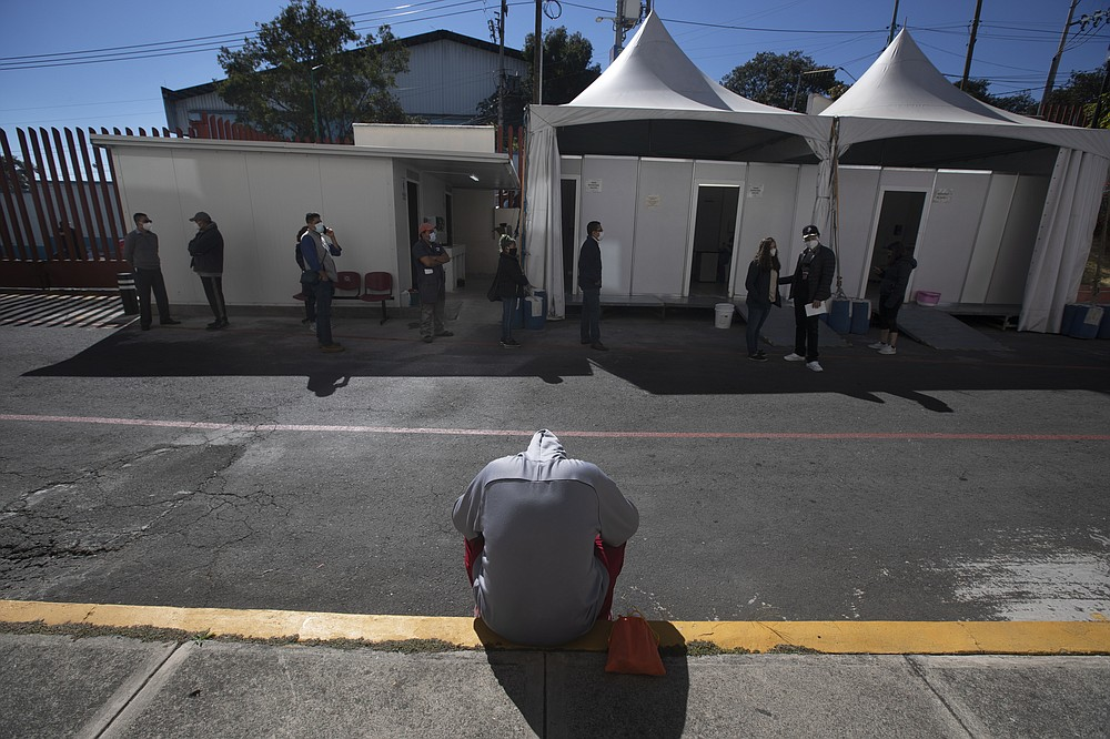 A young man waits to be tested for COVID-19 outside the Ajusco Medio General Hospital in Mexico City, Thursday, Nov. 19, 2020. (AP Photo/Marco Ugarte)