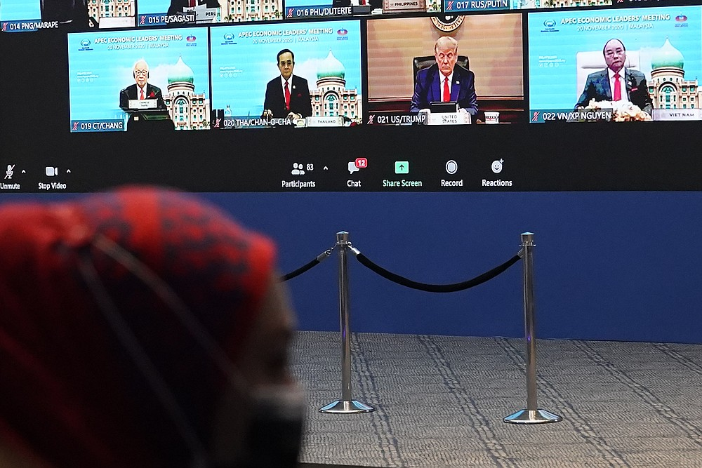 Monitor display showing U.S President Donald Trump, center, together with other leaders attending the first virtual Asia-Pacific Economic Cooperation (APEC) leaders' summit, hosted by Malaysia, in Kuala Lumpur, Malaysia, Friday, Nov. 20, 2020.  Leaders from the Asia-Pacific Economic Cooperation forum have begun a virtual meeting to seek ways to revive their coronavirus-battered economies, with U.S. President Donald Trump participating for the first time since 2017. (AP Photo/Vincent Thian)