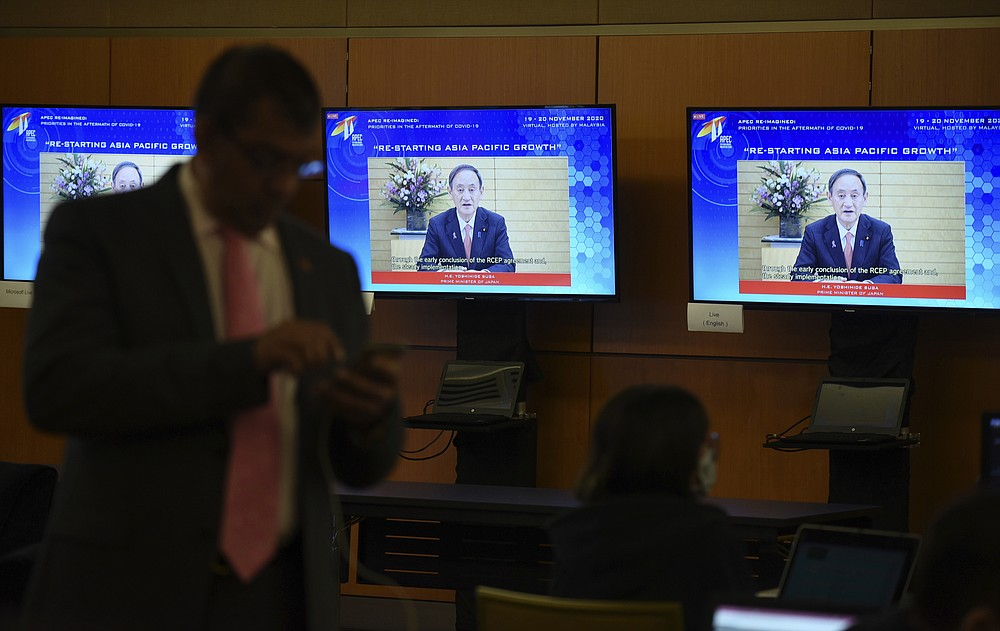 In this photo released by Malaysia Department of Information, screens show Japan's Prime Minister Yoshihide Suga delivering a speech via virtual meeting during the APEC CEO Dialogues 2020, ahead of the Asia-Pacific Economic Cooperation (APEC) leaders' summit in Kuala Lumpur, Malaysia, Friday, Nov. 20, 2020. (Fandy Azlan/Malaysia Department of Information via AP)