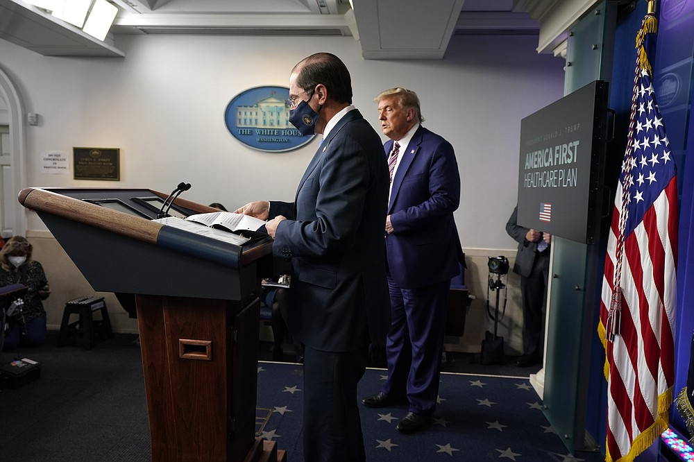President Donald Trump listens as Health and Human Services Secretary Alex Azar prepares to speak during a news conference in the briefing room at the White House in Washington, Friday, Nov. 20, 2020. (AP Photo/Susan Walsh)