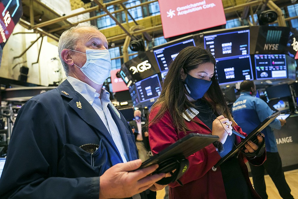In this photo provided by the New York Stock Exchange, traders James Riley and Ashley Lara work on the floor Friday, Nov. 20, 2020. U.S. stocks are pulling a bit lower in midday trading Friday as worries about the worsening pandemic weigh on rising optimism about a coming coronavirus vaccine. (Courtney Crow/New York Stock Exchange via AP)