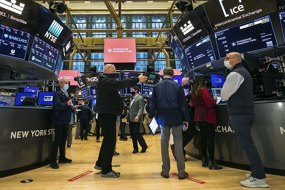 In this photo provided by the New York Stock Exchange, traders work on the floor Friday, Nov. 20, 2020. U.S. stocks are pulling a bit lower in midday trading Friday as worries about the worsening pandemic weigh on rising optimism about a coming coronavirus vaccine. (Courtney Crow/New York Stock Exchange via AP)