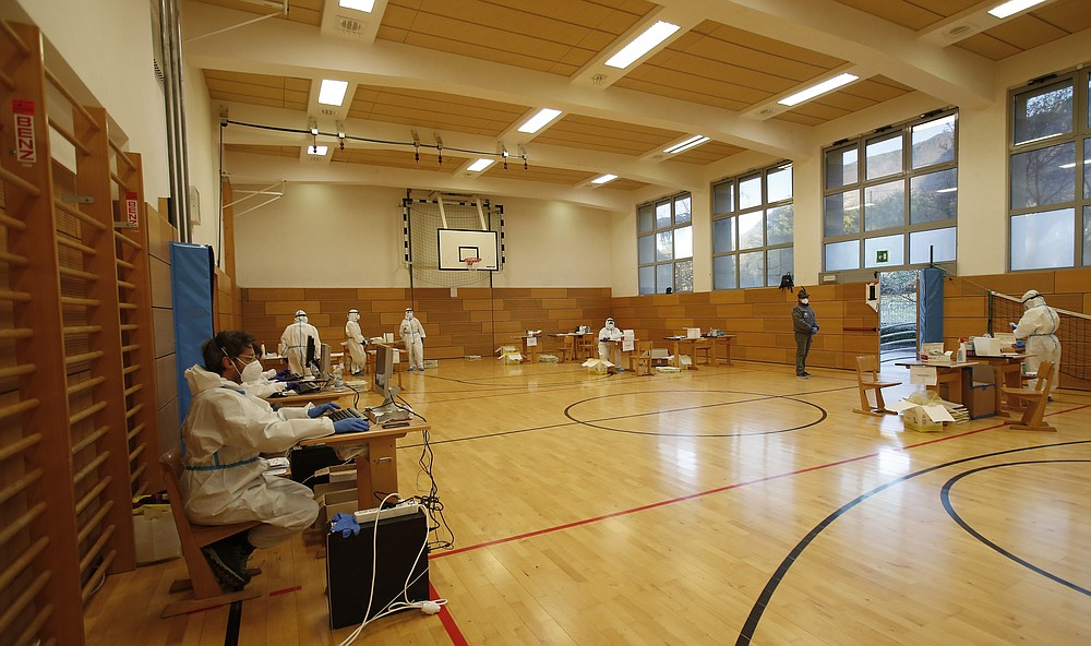 Medical staff members wait for citizens to be tested for coronavirus at a school gym that was set up as a testing facility in Bolzano, northern Italy, Friday, Nov. 20, 2020. Citizens in Italy's small Germany-speaking province of South Tyrol were lining up Friday at schools, gymnasiums and pharmacies for a mass COVID-19 screening that officials hope will speed a lifting of the partial lockdown and get children back to school. (AP Photo/Antonio Calanni)