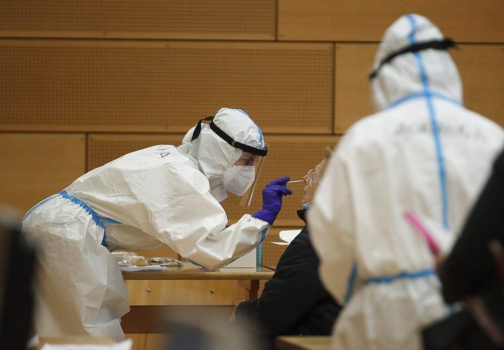 A medical staff member tests a woman for coronavirus at a school set up as a testing facility in Bolzano, northern Italy, Friday, Nov. 20, 2020. Citizens in Italy's small Germany-speaking province of South Tyrol were lining up Friday at schools, gymnasiums and pharmacies for a mass COVID-19 screening that officials hope will speed a lifting of the partial lockdown and get children back to school. (AP Photo/Antonio Calanni)